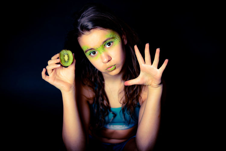 Portrait of beautiful young woman with face paint holding kiwi against black background