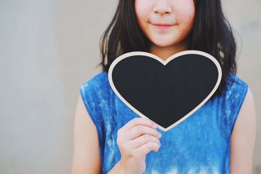 Real People One Person Heart Shape Love Holding Long Hair Copy Space Kid Mother's Day Blackboard  Happy Celebration Holiday Indoors  Smiling Close-up Young Women Blue Happiness Lifestyles Looking At Camera Portrait Women Day Young Adult