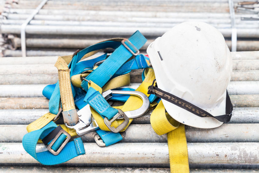 Safety helmet and harness at construction site Construction Site Industry Safety Hard Hat Builders Close-up Dangerous Engineering Equipment Helmet No People Outdoors Protective Workwear Regulation Safety Harness Tools