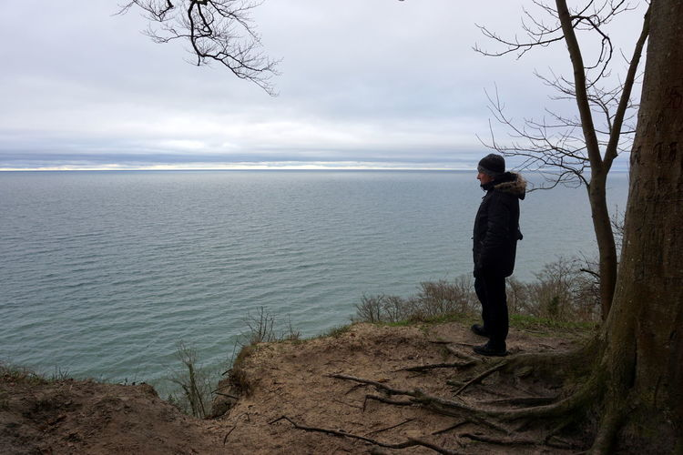 Side view of man looking at sea against cloudy sky