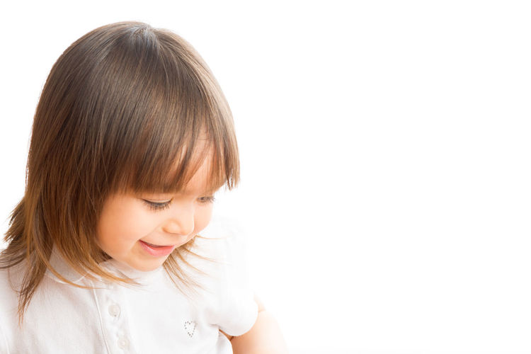 Portrait of a girl looking away against white background