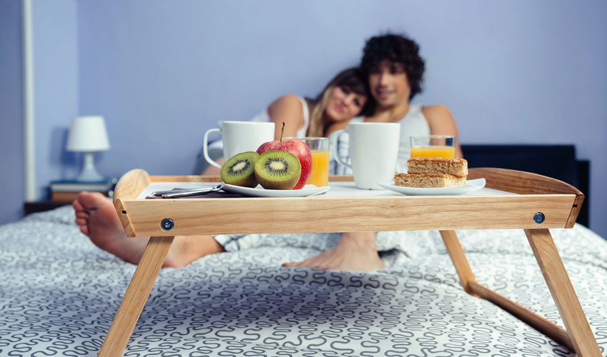 Couple with breakfast on bed at home