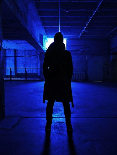 Rear view of silhouette woman standing in illuminated corridor