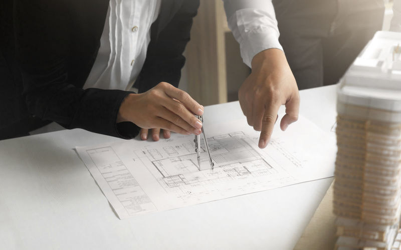 Midsection of architects working on blueprint in office