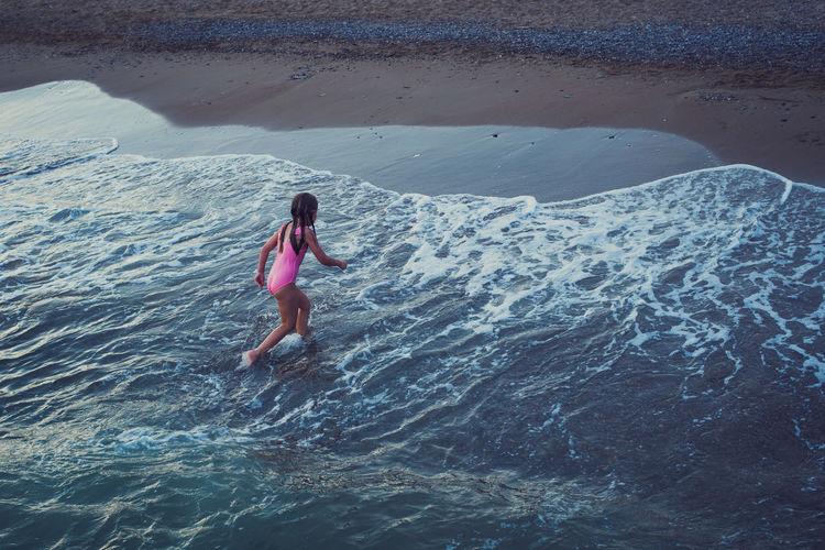 Girl in swimsuir run across the waves