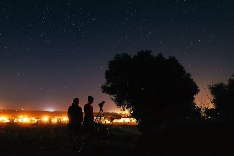 Silhouette female friends standing with telescope on field against star field