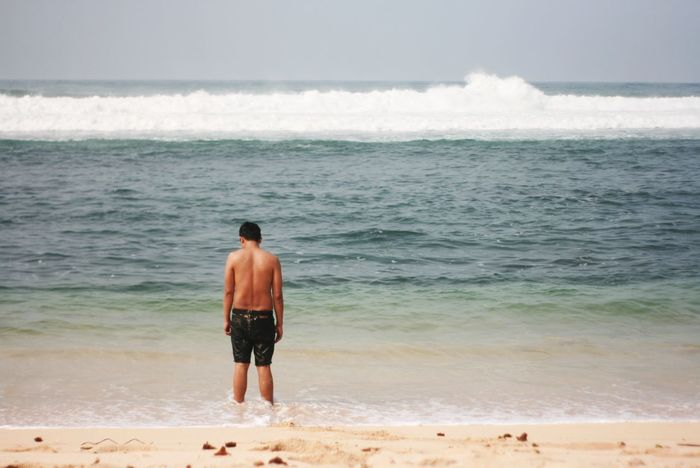 Rear View Of Shirtless Man Standing On Shore Ankle Deep In Water Beach Beauty In Nature Day Full Length Horizon Over Water Leisure Activity Lifestyles Men Nature One Man Only One Person Outdoors Real People Rear View Sand Scenics Sea Shirtless Sky Solitude Standing Vacations Water Wave