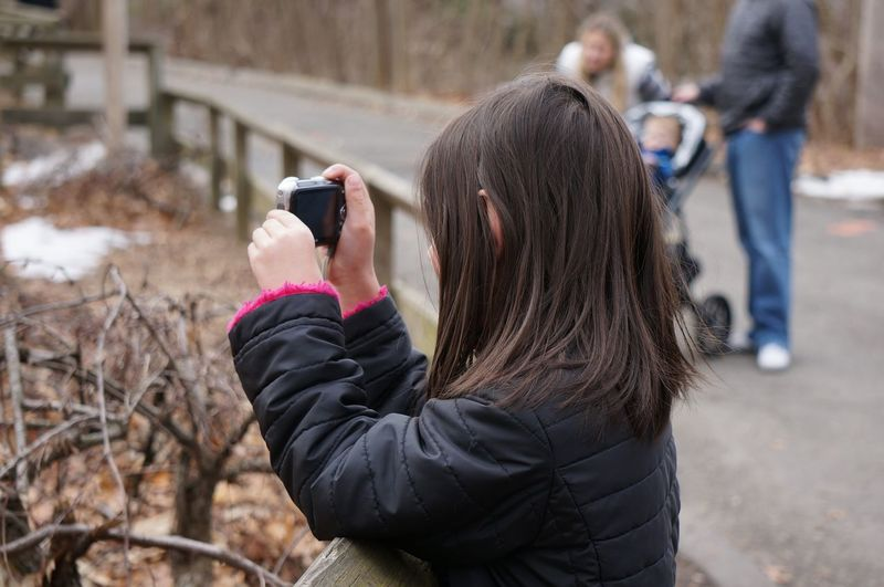 Side view of girl photographing