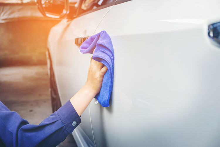 Cropped hand of mechanic cleaning car in garage