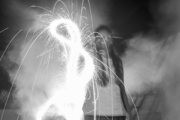 Woman making infinity symbol with fireworks during diwali at night