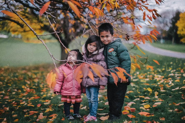 Kids under a tree in Nottingham University Asian  Autumn Nottingham Animal Themes Autumn Bonding Boy Casual Clothing Change Child Childhood Day Friendship Front View Full Length Girl Girls Grass Happiness Kid Leaf Lifestyles Looking At Camera Love Nature Outdoors Portrait Real People Smiling Togetherness Tree EyeEmNewHere EyeEmNewHere