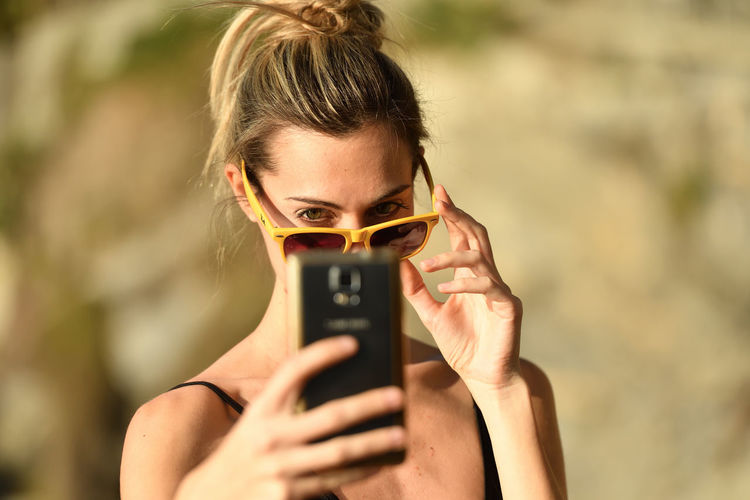 Close-up of young woman using mobile phone outdoors