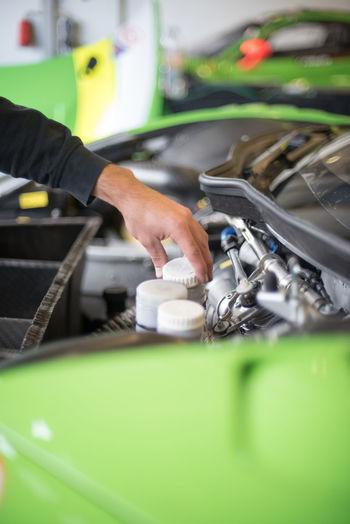 Cropped Image Of Mechanic Examining Car Engine In Garage