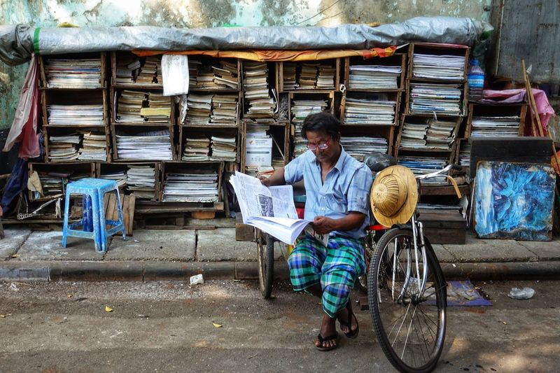 Full length of disabled man reading newspaper while sitting on tricycle
