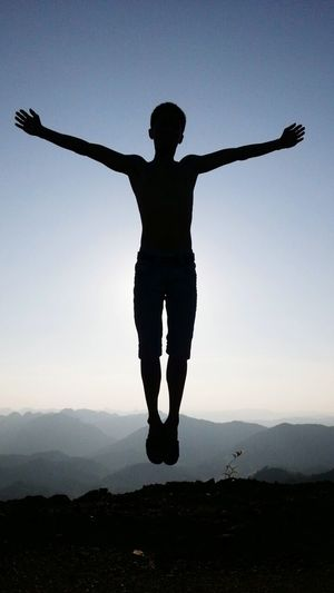Full length of silhouette man on mountain against clear sky