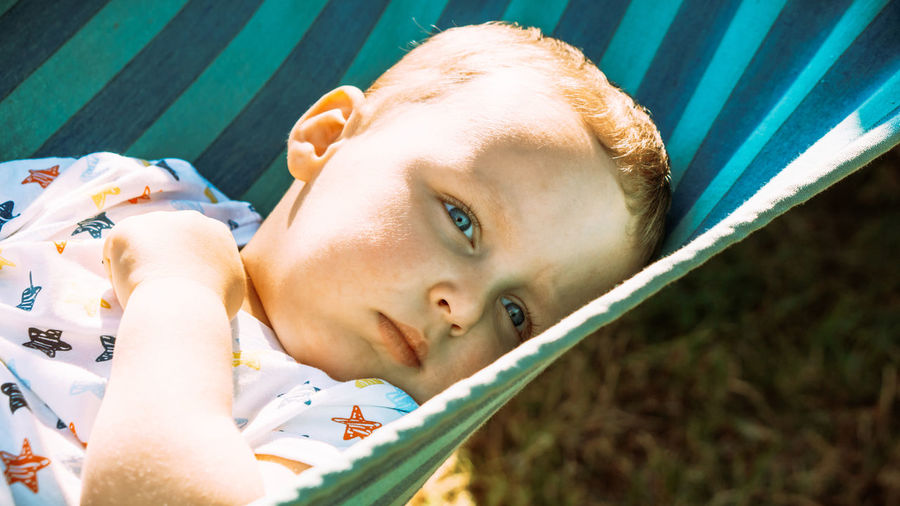 Close-up portrait of cute boy lying outdoors