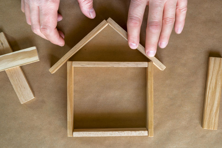 Cropped image of man making wooden figurine house