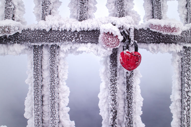Red Heart Shape Lock Attached To Railing During Winter