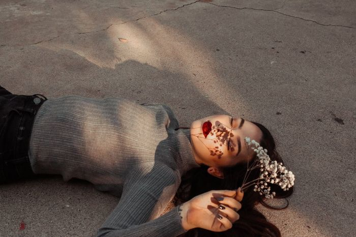 Woman with plant lying down on sand