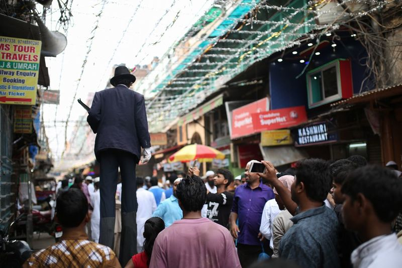 The street showman Group Of People Crowd Architecture City Large Group Of People Real People Building Exterior Men City Life Rear View Lifestyles Communication Street