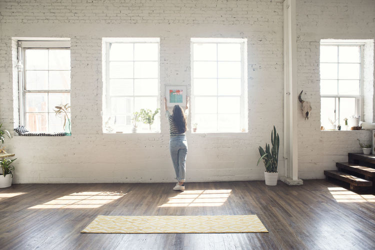 Rear view of woman standing on wooden floor