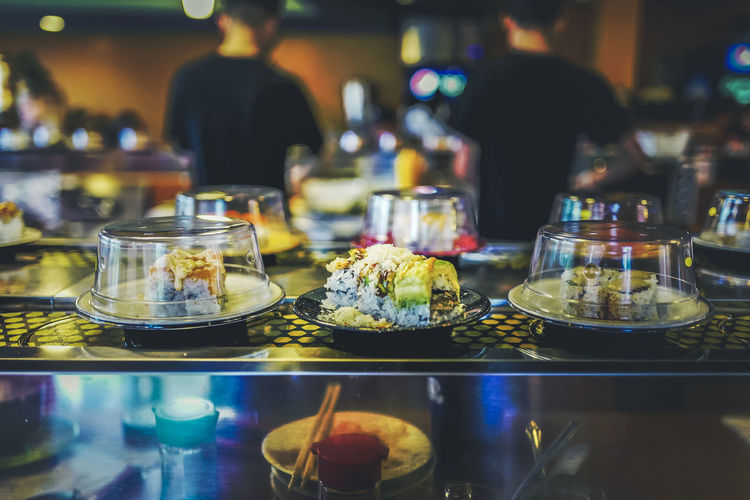 Sushi train Bar - Drink Establishment Bar Counter Business Choice Focus On Foreground Food Food And Drink Freshness Glass Glass - Material Group Of People Illuminated Incidental People Indoors  Plate Ready-to-eat Real People Restaurant Sweet Food Table Temptation Transparent Variation