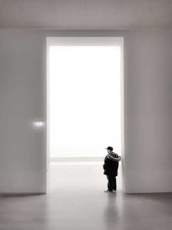 Alone Bright Bright Light Lost Tiny Man Waiting Architecture Black Coat Day Full Length High Doors Indoors  One Person Real People Sad Standing Staring White Background White Ceiling White Flloor