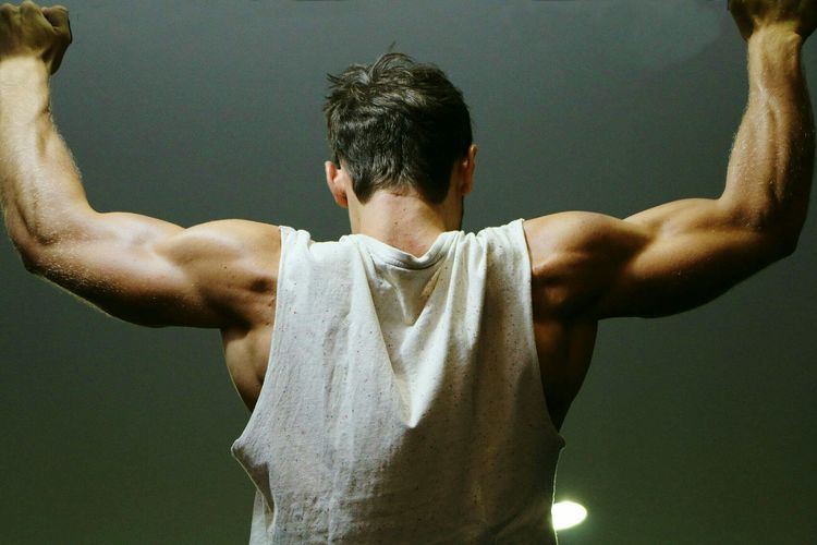 Rear View Of Man Exercising In Gym