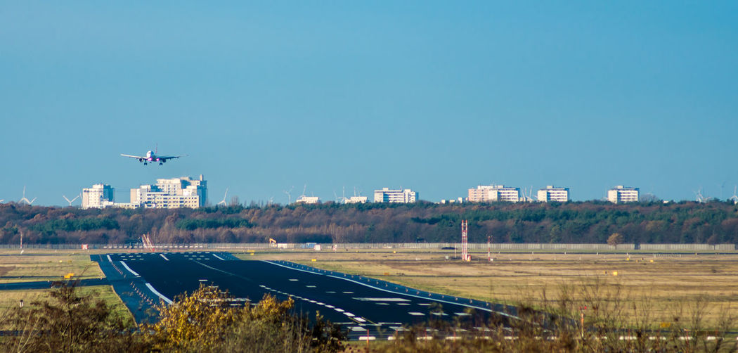 Distant view of airplane landing at airport runway against clear blue sky