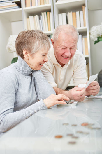 Smiling senior calculating bills on table at home