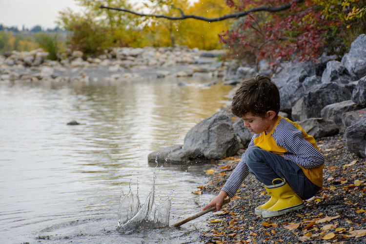 Side view of a boy looking at river