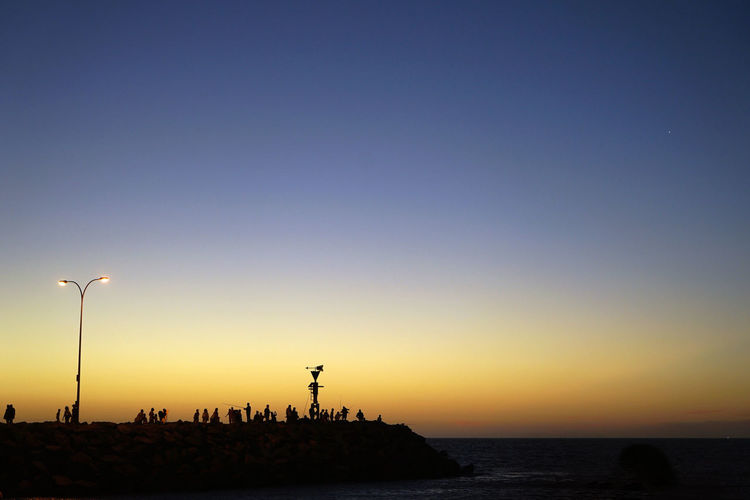 Silhouette People On Pier In Sea Against Clear Sky During Sunset