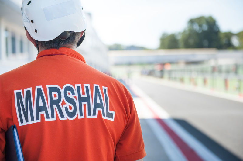 Rear view of motorsport marshal standing at pit stop