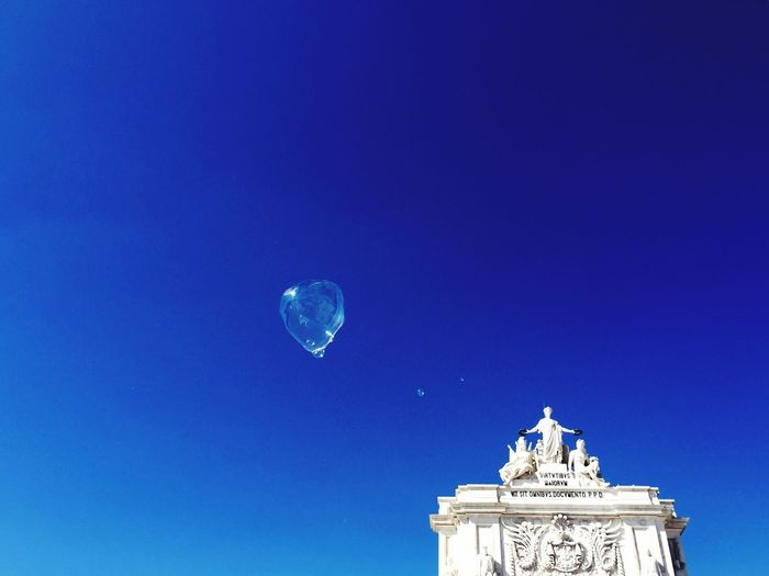 Low angle view of bubble in mid-air against triumphal arch