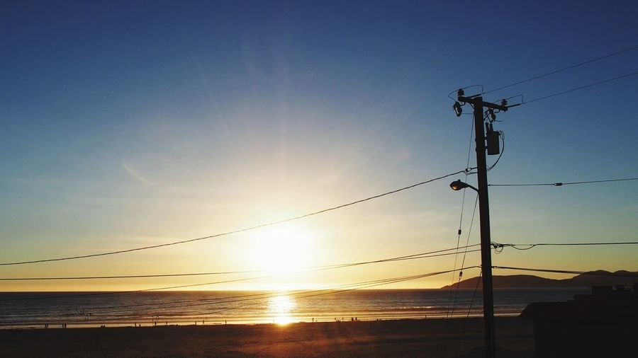 Electricity Pylon At Beach During Sunset