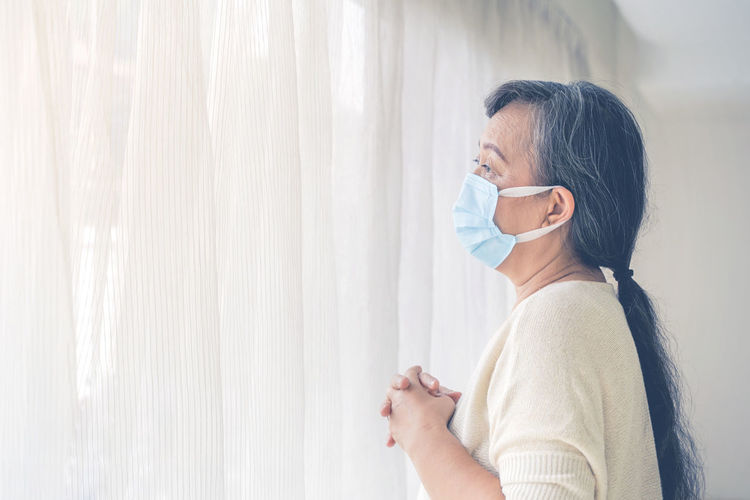 Side view portrait of woman wearing mask standing against window