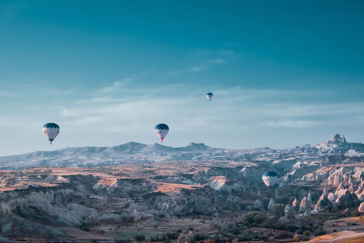 Hot air balloons flying over mountain against sky