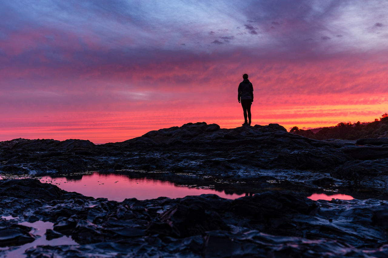 Low Angle View Of Silhouette Person Standing At Mimosa Rocks National Park During Sunset