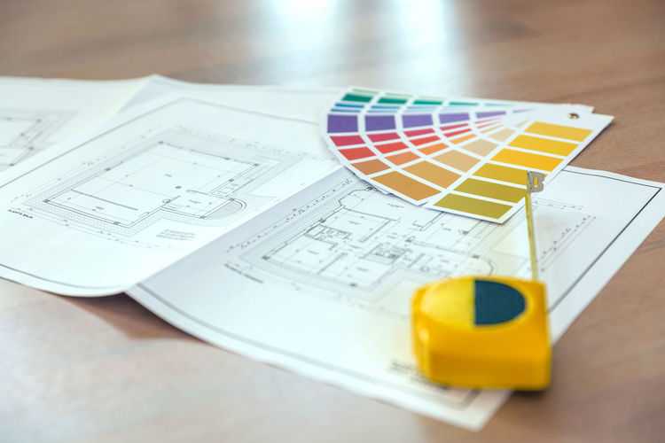 High angle view of color swatch with blueprint and tape measure on wooden table