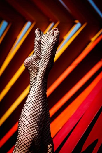 Low section of woman in fishnet stockings