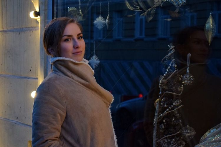Thoughtful woman wearing warm clothing while standing by display cabinet during christmas at night