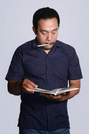 portrait of Asian man with pen in his mouth.selective focus on hand Adult Book Casual Clothing Front View Holding Indoors  Lifestyles Men One Person People Real People Studio Shot White Background Young Adult Young Men