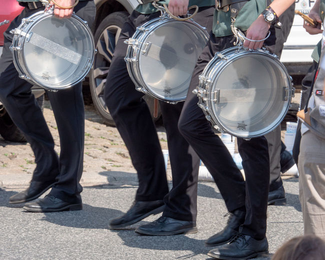 Low section of marching band with drums on street during parade