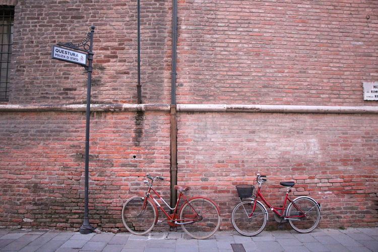 Bicycle parked on footpath against brick wall