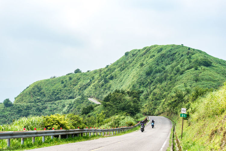 Transportation Road Mountain Plant Sky Tree Day Beauty In Nature Nature Scenics - Nature Mode Of Transportation Green Color Land Vehicle Direction The Way Forward Non-urban Scene Travel Real People Incidental People Mountain Range Mountain Road Outdoors Riding