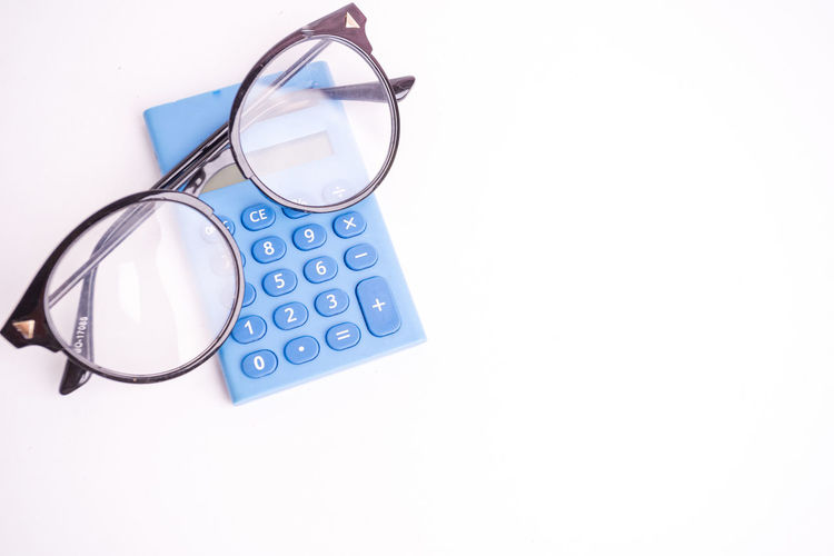 Calculator and spectacles on white background Studio Shot White Background Indoors  Copy Space Eyeglasses  Glasses No People Cut Out Close-up Still Life