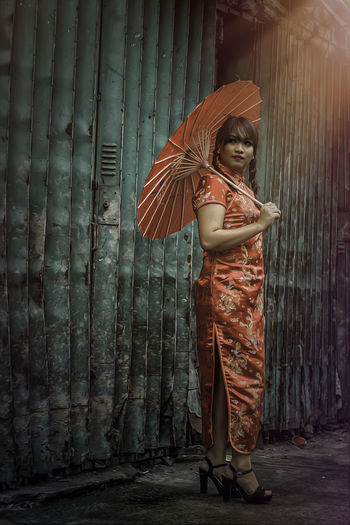 Young woman in traditional clothing holding umbrella by old shutter
