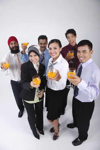 group of people holding glass of orange juice Business Celebration Happiness Indian Teamwork Business Person Chinese Formal Dress  Friendship Full Length Group Of People Harmony High Angle View Malay Malaysian Mixed Race Multi Racial Orange Juice In Glass Portrait Punjabi Smiling Studio Shot Togetherness Turban United