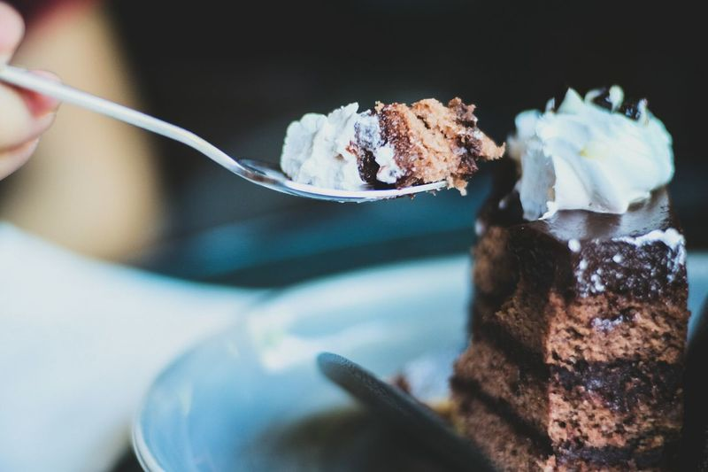 Close-up of person hand holding cake in spoon