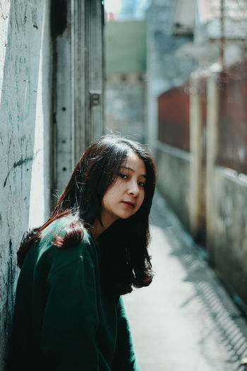 Portrait of woman standing in alley